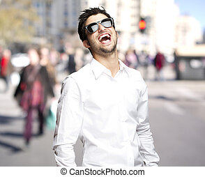portrait of young man with sunglasses laughing at city