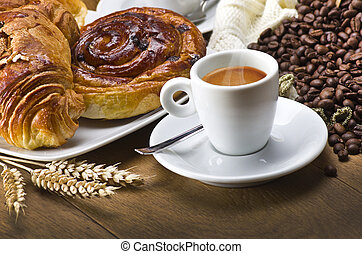 Coffee cup with a croissant and fresh coffee beans on a wood...