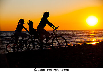 Mother and her kids on the bicycle silhouettes on beach at...