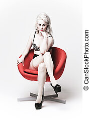 Seductive woman in a red chair - high key image of an...