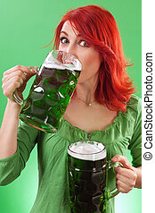 Drinking green beers - Photo of a beautiful redhead holding...
