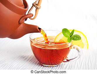 Cup of fragrant tea flowing from a ceramic teapot