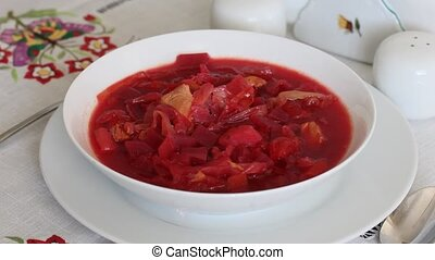 Plate with borsch - red-beet soup on the table