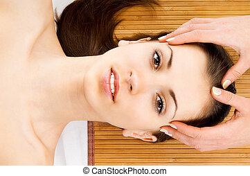 woman receiving facial massage - Beautiful young woman...