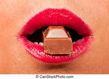 Red, hot lips biting a chocolate