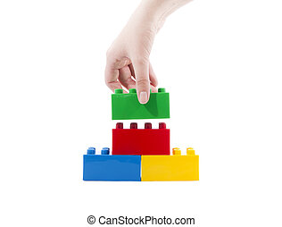 Colorful building toy, and hand. - Construction toys and...