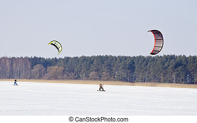 Kiteboarding with snowboards frozen lake in winter