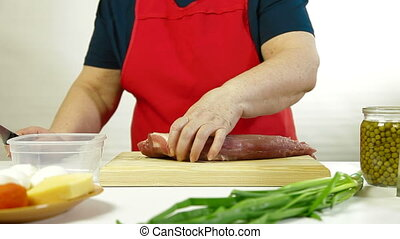 Cutting Pork Tenderloin - Mature woman cutting pork...