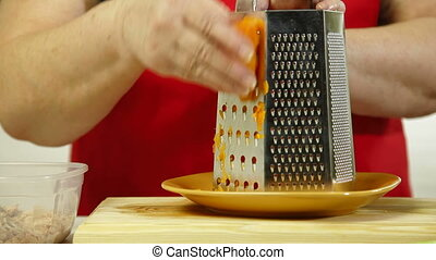 Food Preparation - Grate The Carrot - Mature woman grate the...