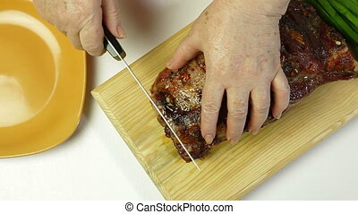 Grilled Tenderloin Pork - Woman cuts off a piece grilled...