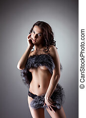 Nude woman in black panties posing with fur coat on breast