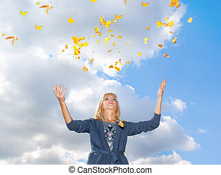 Young woman throwing leaves in the air