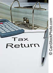 Tax Return - Tax return papers next to folder and calculator...