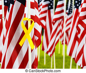 Yellow Ribbon and flags - Closeup of yellow ribbon tied to a...