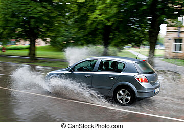 flooded street - A car splashes through a large puddle on a...