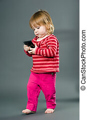 Cute little girl with mobile phone on gray background