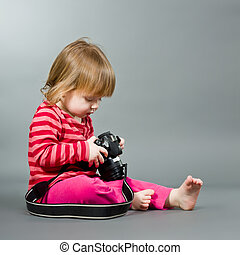 Cute little baby with digital photo camera