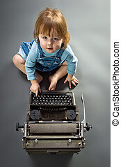 Cute little baby with retro style typewriter in studio