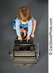 Cute little baby with retro style typewriter