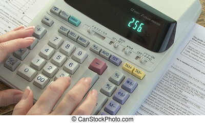 Doing Taxes - Woman using adding machine while doing taxes