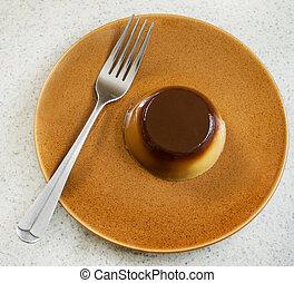 caramel flan - one small caramel flan dessert on a plate