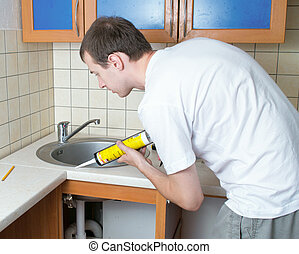 Plumber putting a silicone sealant to installing a kitchen...