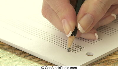 Woman writing music notation - Close up of woman writing...