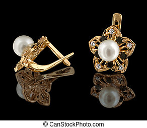 gold earrings with diamonds and pearl isolated on black...