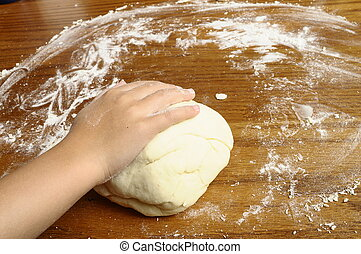 Child's hands kneading bread dough on wooden table with flour