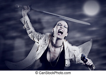Portrait of young sexy woman vampire holding medieval sword...
