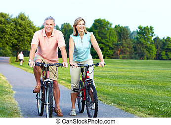 Senior couple cycling. - Happy senior couple cycling in the...