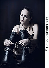 Sad woman in long black boots with bandage on hands and legs