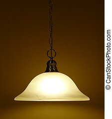 HANGING LAMP - An indoor hanging incandescent lamp against a...