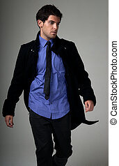 Young man fashion suit walking over grey