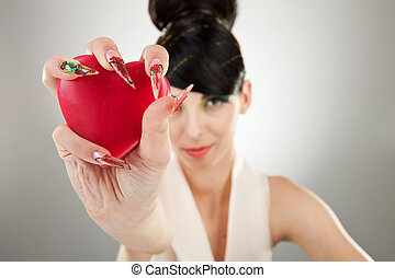 woman holding heart in one hand