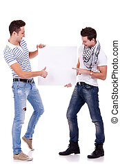 two young men holding a blank board on white background, one...