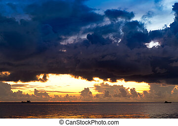 Sunset at South China Sea with threatening sky and ships,...