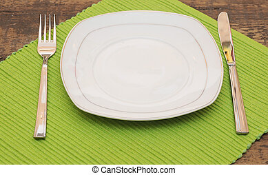Empty dish, knife and fork and green napkin on wood table