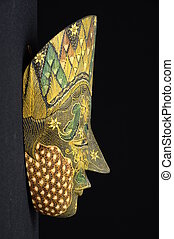 Profile view of an asian mask on black background painted with flowers patterns