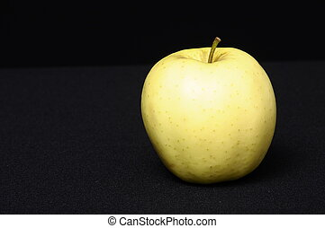 Gold apple on a black background