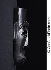 Profile view of a african black wood mask on a black background