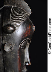 Profile wiew of an african wood mask on black background