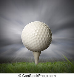 closeup of golf ball on golf tee with stormy fast moving sky...