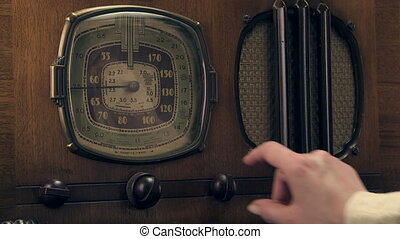 1930's vintage radio - Woman's hand turning on and tuning a...