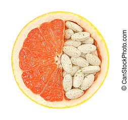 Close up of red grapefruit and pills isolated - vitamin...