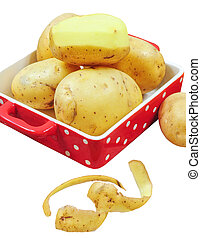 Raw potatoes in red tray and potato peels, isolated