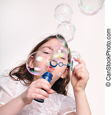 child blowing bubbles with bubble wand - Little girl playing...