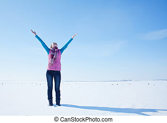 Teen girl staying with raised hands against blue sky