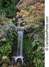 A small waterfall in the pond in the Japanese garden in...
