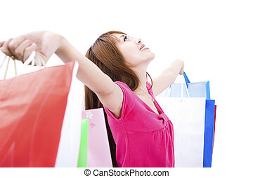 young woman holding shopping bag and looking up